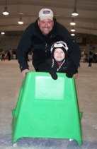 Dad and child skating during public skate at the Ice Arena